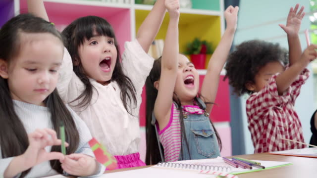 Slow motion - Group of children drawing in classroom, Multi-ethnic young boys and girls happy funny study and play painting on paper at elementary school. Kids drawing and painting at school concept.