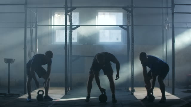 slow motion: group training three athletes in an atmospheric fitness room against the background of the rays of sunlight lift up kettlebell - giria filmów i materiałów b-roll