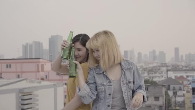 vidéos et rushes de slow motion - gens de jeunes femmes asiatiques du groupe dansant et levant les bras vers le haut dans l'air à la musique jouée par dj lors d'une fête urbaine coucher de soleil sur le toit. amis de jeunes filles asiatiques traîner avec bière boisso - fête de naissance