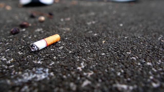 slow motion: guy puts out a cigarette foot on the road - sigaretta video stock e b–roll