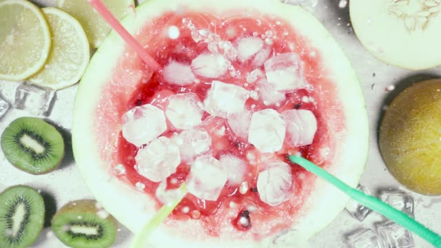 vídeos de stock e filmes b-roll de slow motion half of watermelon with the juice falling ice top view - kiwi