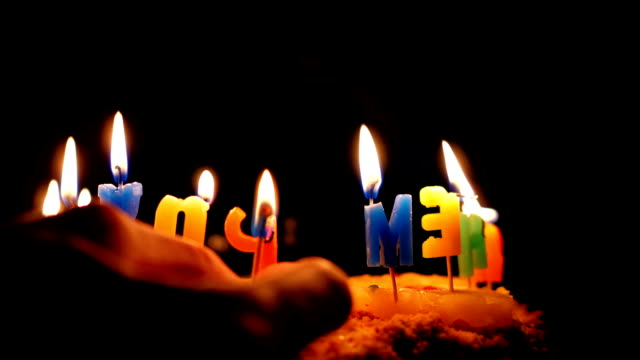 slow motion hand inserts burning match on cake in darkness