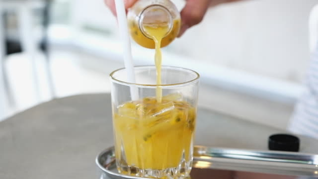 slow motion hand pour passion fruit drink into ice in glasses - passiflora video stock e b–roll