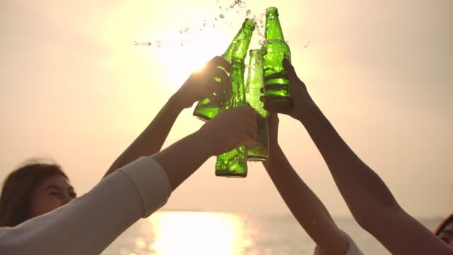 슬로우 모션 손 은 일몰, 승리, 축하에 해변에서 맥주 병을 토스트 - 경례 스톡 비디오 및 b-롤 화면