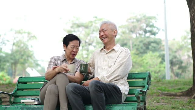 Slow motion happy Asian senior couple sitting and drinking tea, coffee in morning park. Having conversation and showing love video