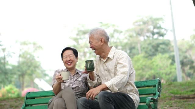 スローモーション幸せなアジア シニア カップルに座って、お茶、公園の朝のコーヒーを飲みます。会話と愛を示す - シニア点の映像素材/bロール