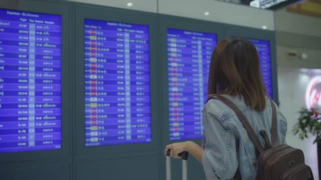 vídeos de stock, filmes e b-roll de câmera lenta - mulher asiática feliz olhando para informações placa verificando seu voo com bagagem em terminal hall, o portão de embarque no aeroporto internacional. mulheres de estilo de vida felizes no conceito de aeroporto. - voando