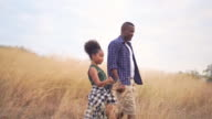 istock HD Slow motion Happy family African father and daughter hiking and holding hands together. Relaxing father and pretty daughter talking and walking together on golden meadow grass field in summertime 1205648494