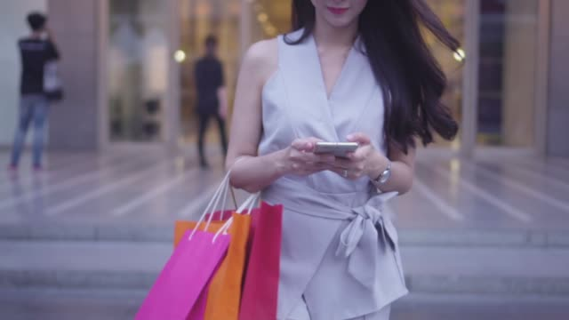 slow motion : happy young girl is walking in a department store and texting a message on a smartphone. - borsa della spesa video stock e b–roll