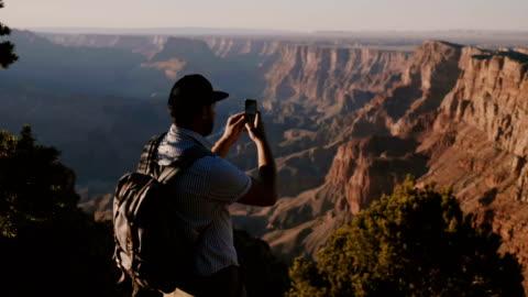 slow motion felice giovane turista con zaino che scatta foto per smartphone dell'epico tramonto estivo sul grand canyon usa. - canyon video stock e b–roll