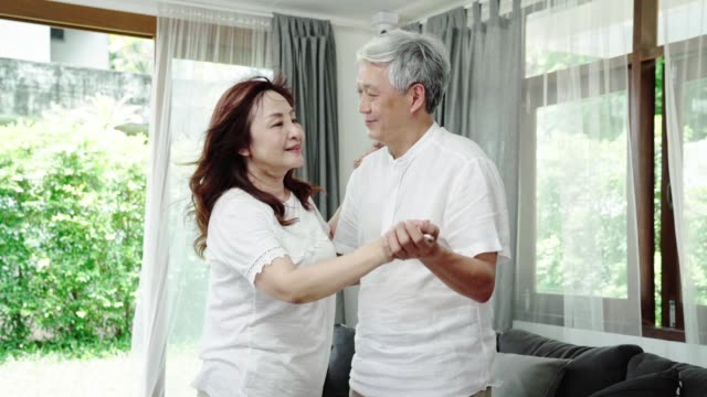 Slow motion HD : Asian seniors couple dancing in living room at home. Aging lifestyle concept