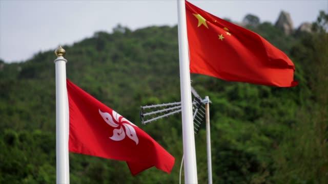 ağır çekim hong kong ve çin bayrakları rüzgarda sallanan - cumhuriyet günü stok videoları ve detay görüntü çekimi