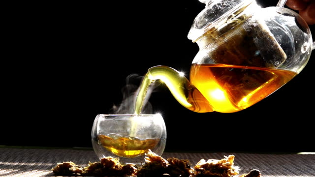 Slow motion, hot chrysanthemum tea that is poured from a glass jar into a cup of white smoke from heat. video