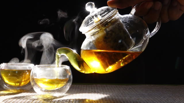 Slow motion, hot chrysanthemum tea that is poured from a glass jar into a cup of white smoke from heat.