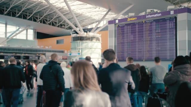 vídeos y material grabado en eventos de stock de slow motion enorme tablero de información en el aeropuerto internacional. a su alrededor son turistas no reconocidos, borrosos y viajeros con maletas. esperando la salida y el embarque - largo longitud