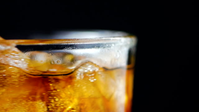 slow motion ice and liqueur brandy in the glass - scotch whisky video stock e b–roll