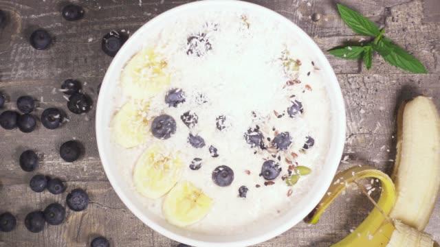 Slow motion dans un bol de Smoothie aux fruits drop vue de dessus de noix de coco - Vidéo
