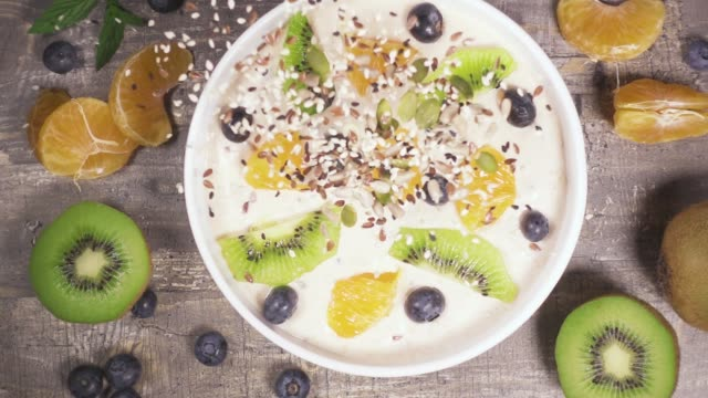 slow motion in a bowl of fruit yogurt smoothie drop the mixture of sesame seeds top view - smoothie filmów i materiałów b-roll