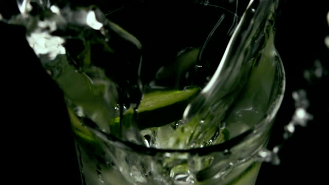 Slow motion. In a glass of water drops ice and cucumber video