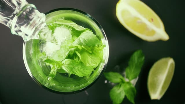 Slow motion in a glass with ice and mint pour water