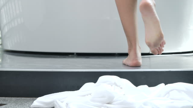 4K Slow motion In the morning, the woman walked to the bathtub and took off the white robe to take a shower.