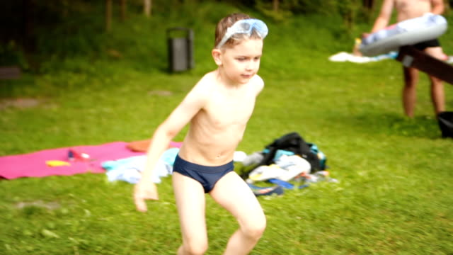 slow motion: kid enters the lake by running - young singles stock videos and b-roll footage
