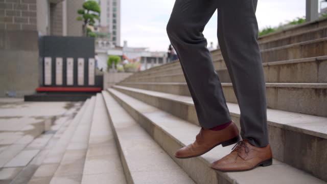 オフィス地区のラッシュアワーに階段を歩くスーツと革靴を着たコンフィデンスビジネスマンのサラリーマンのスローモーションレッグ。ビジネスマン起業家は、市内の階段を降りる。 - 階段点の映像素材/bロール