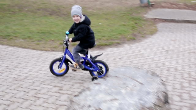 Slow motion. Little boy in a gray hat and warm jacket riding a blue bicycle on the playground. video