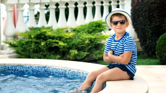 Slow motion little boy in sunglasses and hat sitting on edge of swimming pool playing legs in water