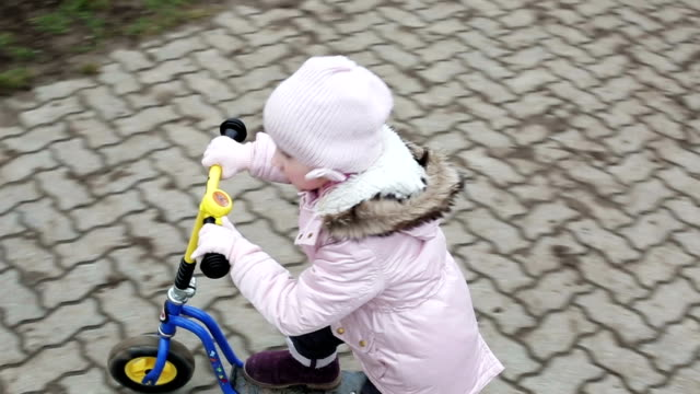Slow motion. Little girl in a warm hat and jacket riding a mini scooter outdoors. video