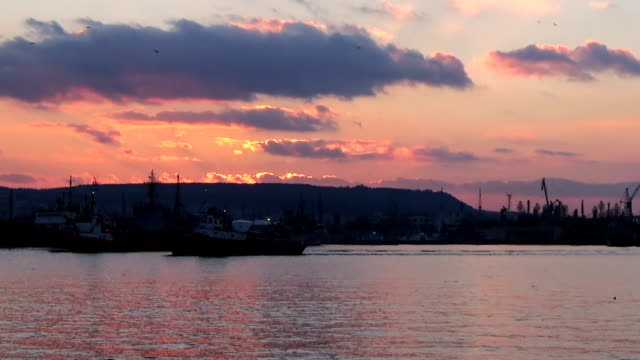 Slow motion long shot of Varna harbour at sunset pink sky with darker clouds video