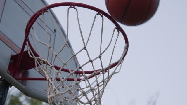 vídeos y material grabado en eventos de stock de disparo de mano artístico de ángulo bajo de cámara lenta de una alta canasta de gol de baloncesto al aire libre bajo un cielo gris claro en una noche de verano alrededor de la hora dorada de la puesta del sol - basketball hoop