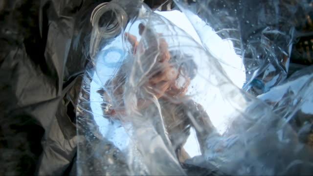 zeitlupe low angle view junger mann sammeln plastikflaschen aus papierkorb - altglas stock-videos und b-roll-filmmaterial
