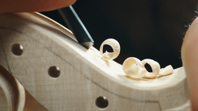 Slow motion macro of master artisan luthier painstaking detailed work on wood violin in a workshop Slow motion macro of master artisan luthier painstaking detailed work on wood violin in a workshop. Shot in 8K. Concept of spiritual instrument, handmade, art, orchestra, artisan, passion for music classical concert stock videos & royalty-free footage