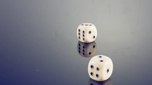 slow motion macro shot of white dice falling and rolling on reflective surface - rotolo video stock e b–roll