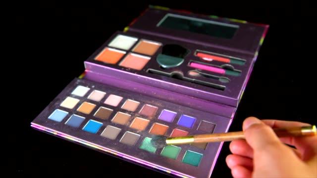vídeos de stock e filmes b-roll de slow motion pov of makeup brush application with makeup palette on black background - sombra para os olhos
