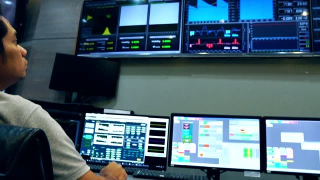 slow motion: male asian engineers are operating in a regulated electricity system - centrale elettrica video stock e b–roll