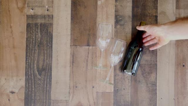 スローモーション、男性の手が赤ワインボトルをつかみ、ガラスで木製のテーブルから - 赤ワイン点の映像素材/bロール
