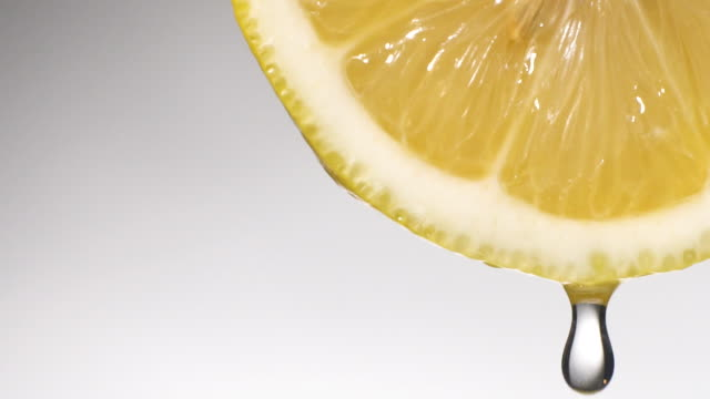 Slow motion: Many liquid drop from lemon slice on white