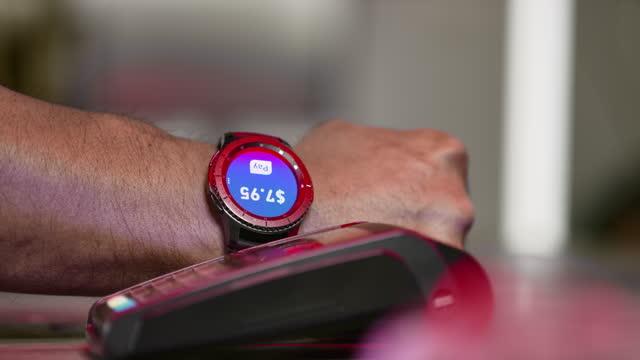 slo mo ld cliente che effettua un pagamento contactless con uno smartwatch - computer indossabile video stock e b–roll