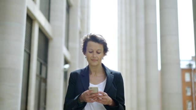vídeos y material grabado en eventos de stock de tiro medio lenta mujer de mediana edad de mensajería de texto en el teléfono celular mientras caminaba por la calle en día de viento - cabello corto
