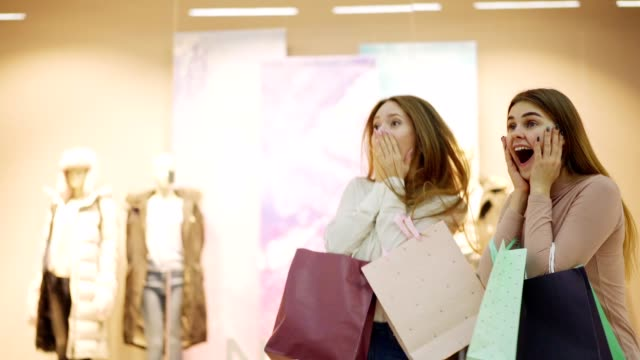 vídeos de stock e filmes b-roll de slow motion medium shot of two overexcited young women with shopping bags shouting and talking emotionally while pointing at window displays in shopping mall on sales day - black friday