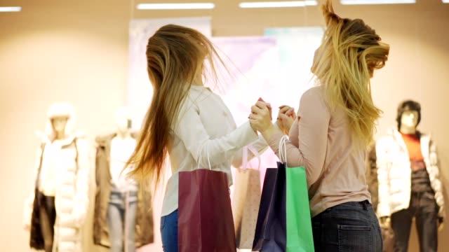 stockvideo's en b-roll-footage met slow motion medium shot van twee shopaholic jonge vrouwen met boodschappentassen krijgen gek in winkelcentrum op verkoop dag. vriendinnen schreeuwen, wijzend op venster displays en knuffelen in opwinding - black friday shop