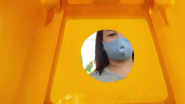 Slow motion, middle-aged throwing plastic bottles into recycling bins video