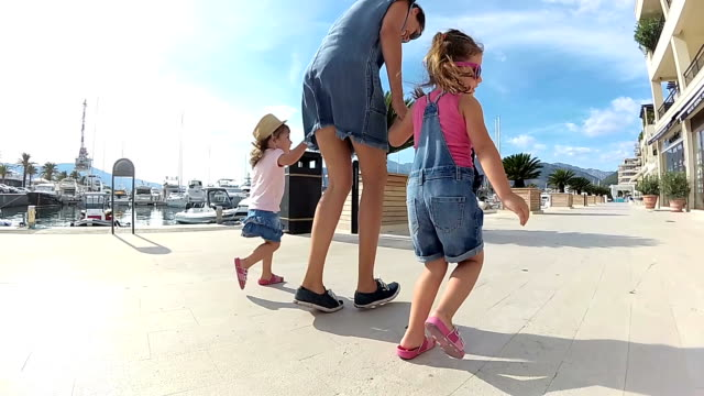 slow motion mother and daughters on vacation walking in the port in porto montenegro - mika video stock e b–roll