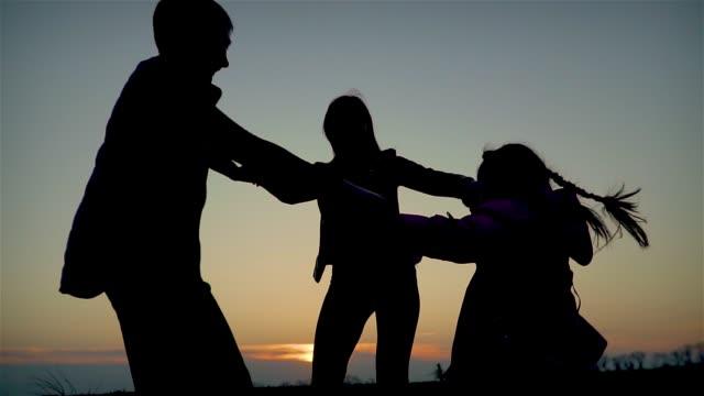 Slow motion mamma med sina barn son och dotter håller händer och glatt spinning i naturen i solstrålar på kvällen video