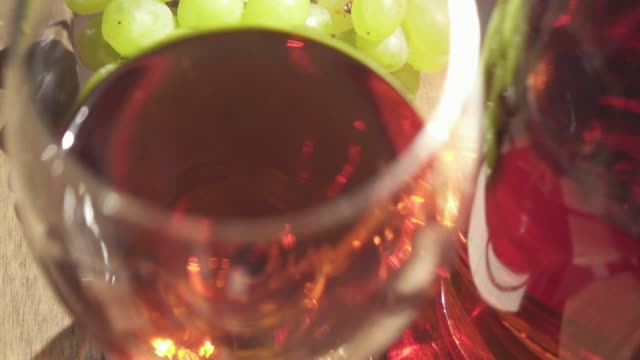 Slow motion movement of the camera over a table with wine and grapes Slow motion movement of the camera over a wooden table with bunches of grapes and wine in a bottle and a glass cork stopper stock videos & royalty-free footage