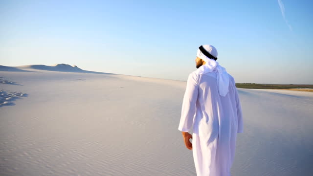 Slow motion movements of Arabian UAE Sheikh guy to top of sandy hill over white sand in desert on clear day
