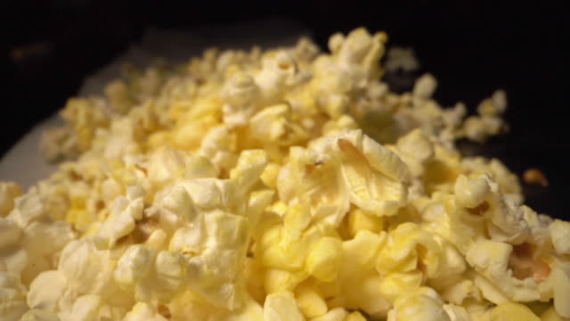 Slow Motion Moving Camera Wide Angle Moving Shot of Heap of Fresh Buttery Greasy Yellow Popcorn on a Counter Top