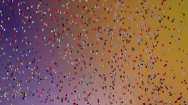 slow motion: multi färg korn faller och studsar på gradient färg bg - confetti bildbanksvideor och videomaterial från bakom kulisserna